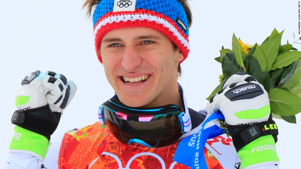 Golden boy: Matthias Mayer of Austria celebrates on the podium after winning the men's downhill in Sochi.