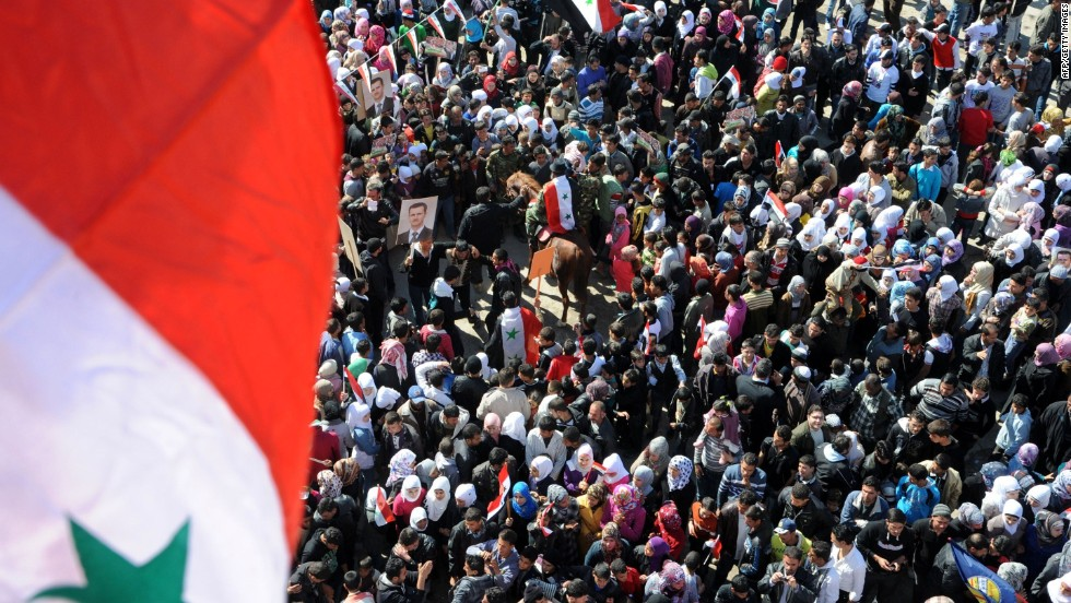 In this handout photo released by the state-run SANA news agency on February 8, civilians wave national flags in Damascus as they take part in a rally in support of President al-Assad.