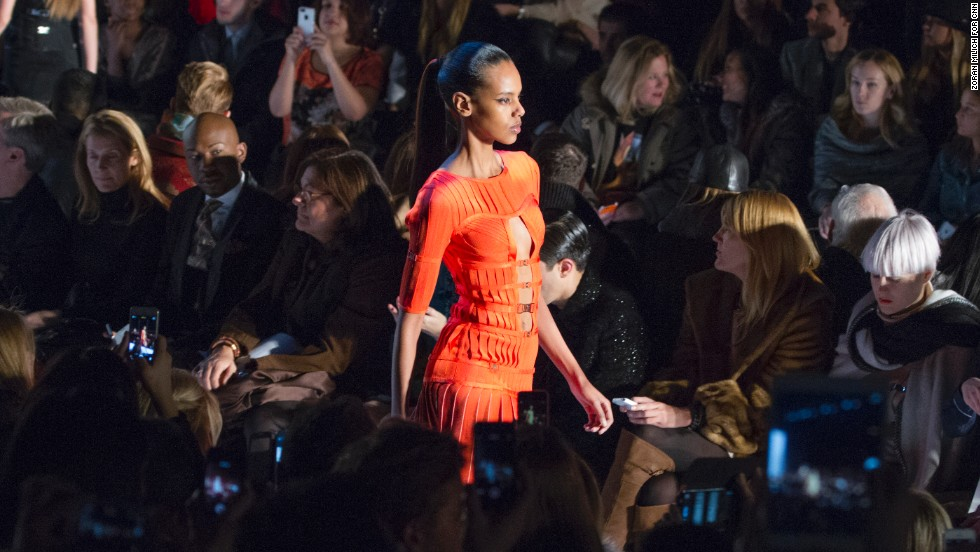 A model walks down the runway in a burst of orange at Herve Leger.