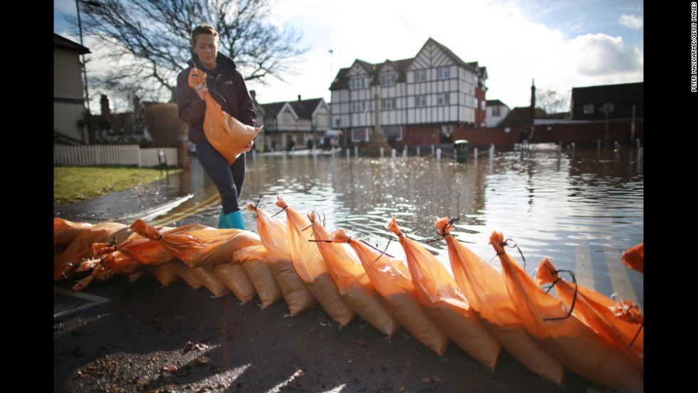 A Datchet resident builds a flood wall with sandbags on February 10.