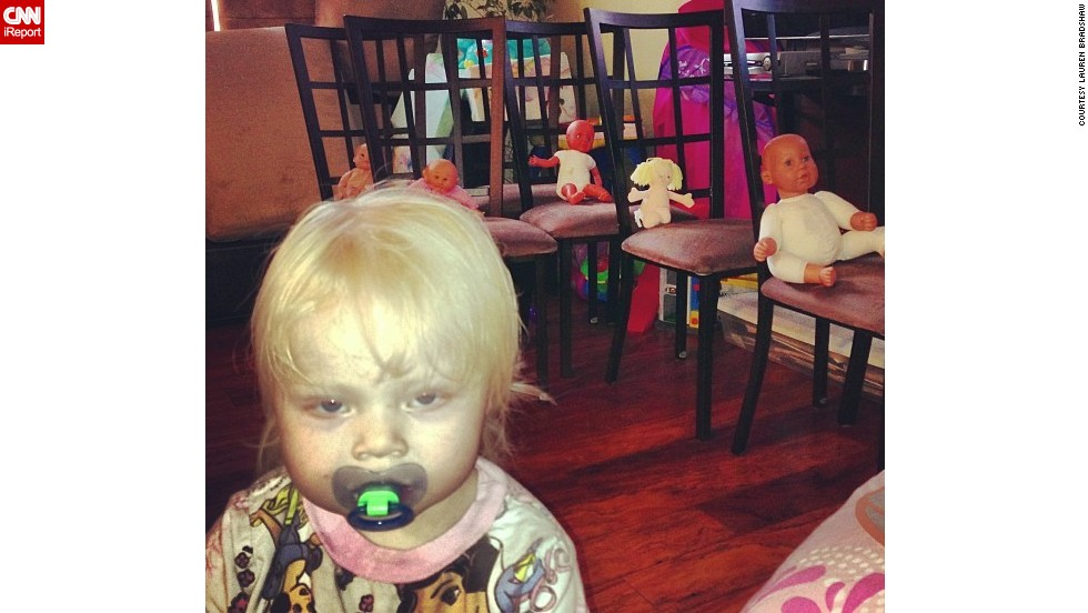 """Be afraid. Be very afraid."" -- Brooke Bradshaw, age 2, after moving all of the kitchen chairs into the living room and carefully placing a doll on each chair.  Mom, Lauren Bradshaw, admits there's ""something a little creepy about this photo bomb."""