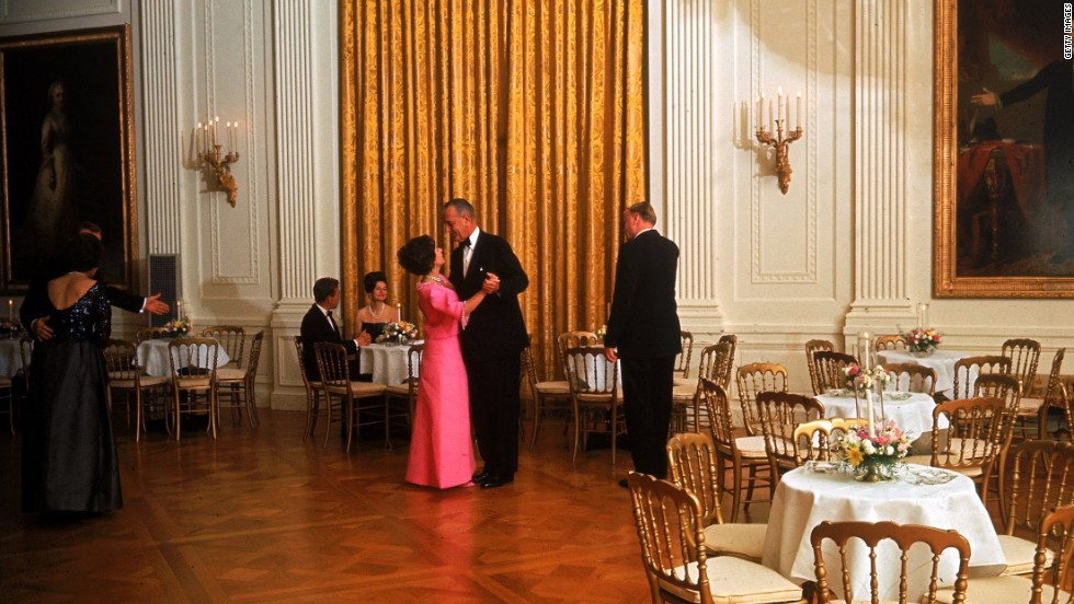 President Lyndon Johnson dances with Princess Margaret at a state dinner for her and her husband, Anthony Armstrong-Jones, seated at table at left, and first lady Lady Bird Johnson on November 17, 1965.