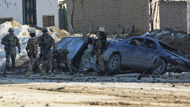 U.S. soldiers and Afghan security forces search the site of a suicide bombing in Kabul, Afghanistan, on February 10, 2014.