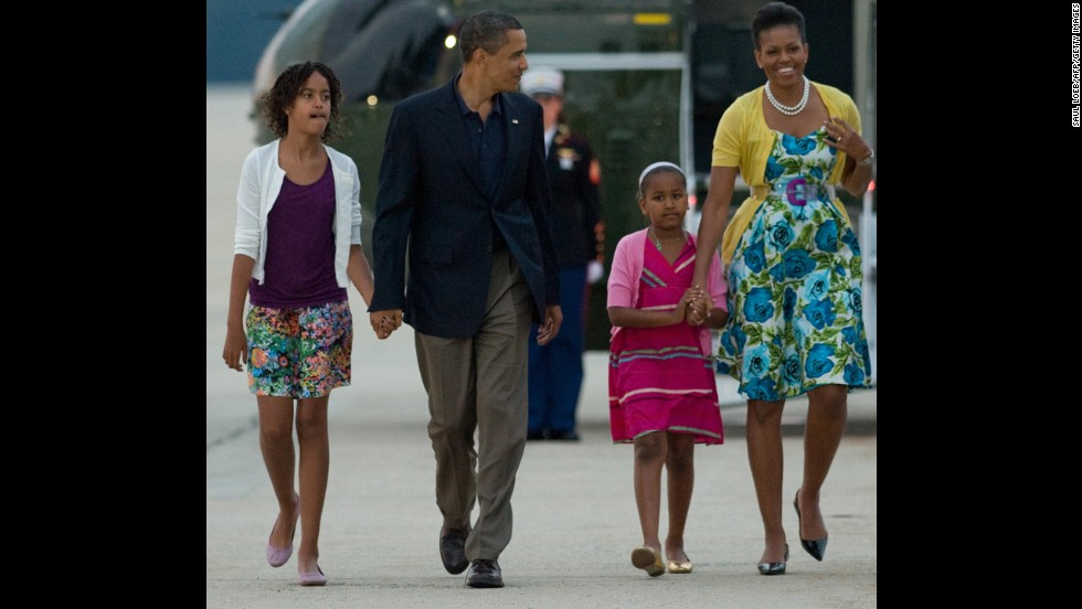 In 2009, President Barack Obama walks with daughters Sasha and Malia and first lady Michelle Obama -- all wearing cardigans. Michelle Obama wears a sweater from Dear Cashmere, a belt by Sonia Rykiel and a dress from Talbots.