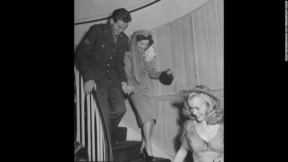 Temple and John Agar walk down a staircase after their wedding in 1945. The couple divorced in 1950.