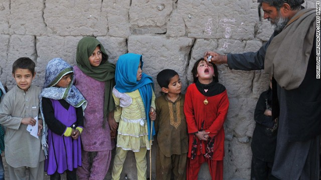 An Afghan health worker administers a polio vaccination to a child in Nangarhar province on January 26, 2014.