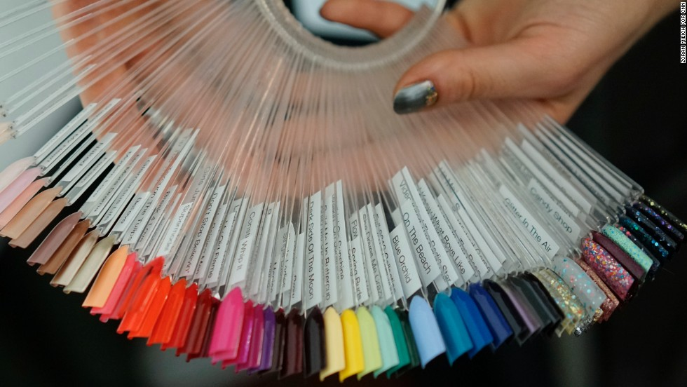 A nail artist shows off swatches of different polish colors before the Badgley Mischka show.