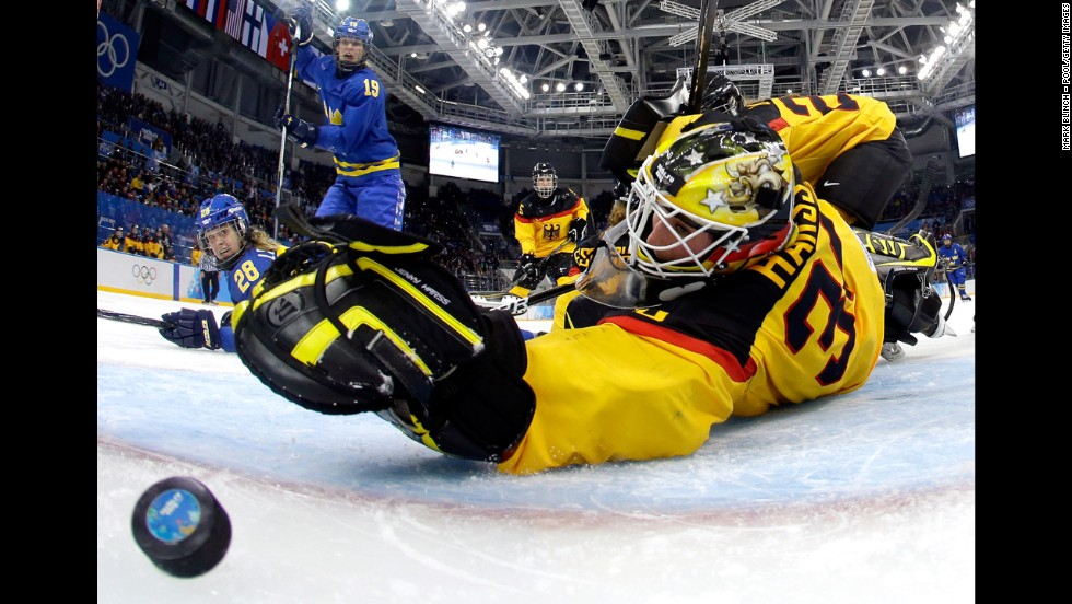 Michelle Lowenhielm of Sweden scores against Jennifer Harss of Germany in the third period of their hockey game on February 11.