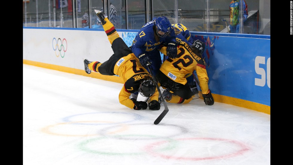 Linnea Backman of Sweden, center, fights for the puck against Nina Kamenik, left, and Kerstin Spielberger of Germany during their Group B hockey game on February 11.