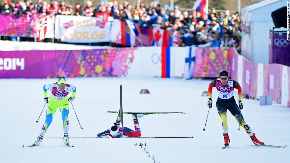 Norway's Marit Bjoergen falls as she competes with Katja Visnar of Slovenia, left, and Denise Herrmann of Germany during the finals of the women's cross-country sprint on February 11.