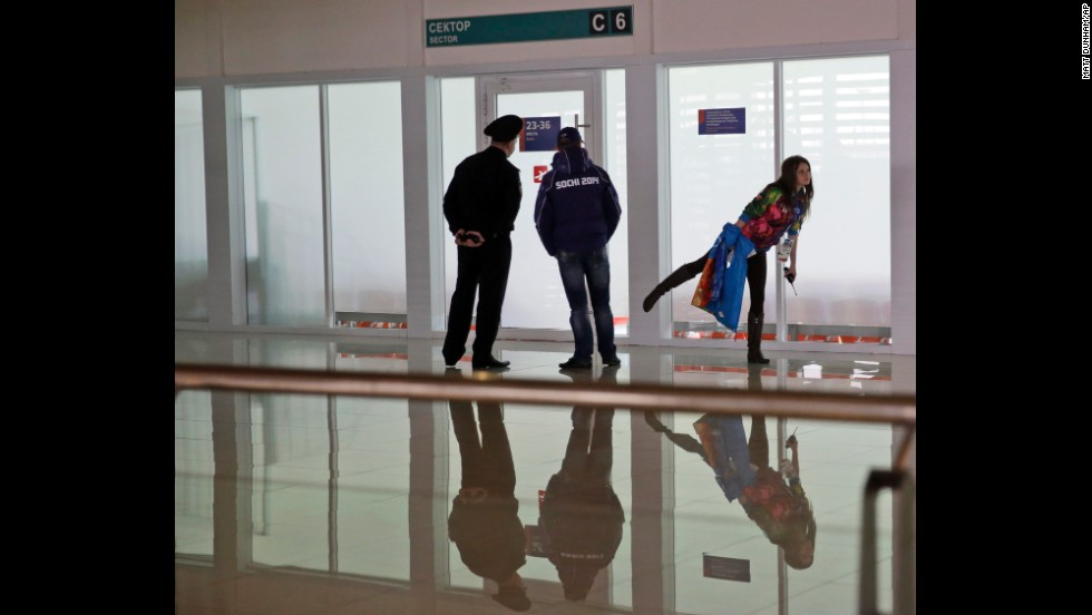 A girl balances on one leg as security personnel stand guard before the start of the women's 500-meter speedskating race in Sochi on Tuesday, February 11.