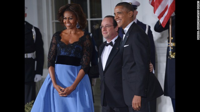 President Barack Obama and first lady Michelle Obama pose with French President Francois Hollande as he arrives for the state dinner at the North Portico of the White House  in Washington, DC.