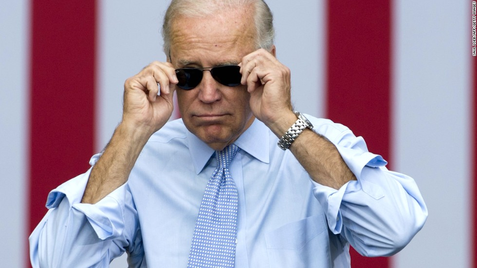 Joe Biden removes his sunglasses as he arrives for a campaign event with President Obama in Portsmouth, New Hampshire, in September 2012.