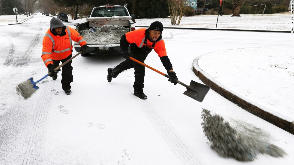 City workers spread a mixture of sand and salt on an intersection in Avondale Estates, Georgia, on February 12.