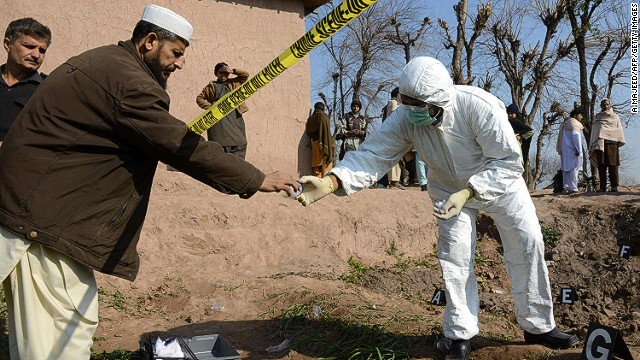 Pakistani security officials inspect the site of an attack by militants in Peshawar on February 12, 2014.