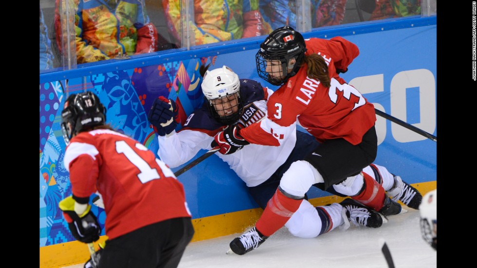Canada's Jocelyne Larocque, right, checks Megan Bozek of the United States during their hockey game.