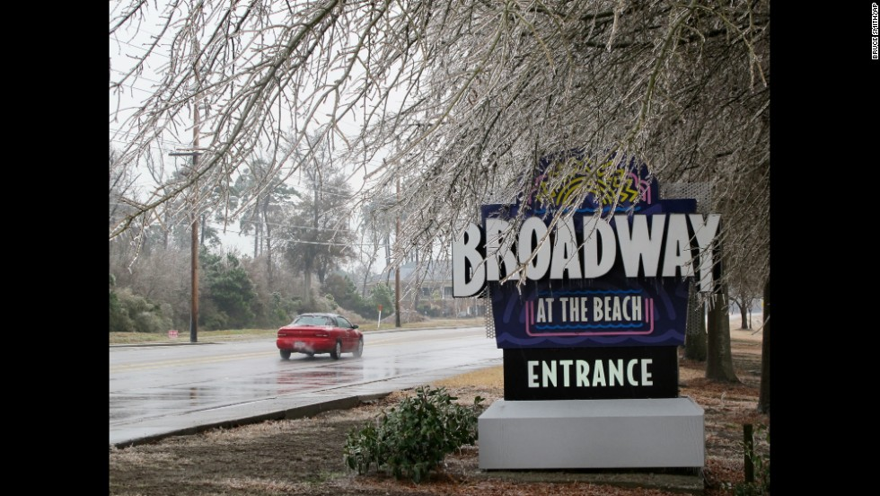 Ice coats trees hanging over a sign for the Broadway at the Beach tourist attraction in Myrtle Beach, South Carolina, on February 12.