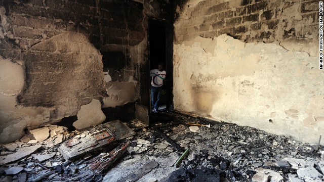 A man inspects a destroyed room at Libya's Al-Asema TV station in Tripoli after it was attacked February 12, 2014.