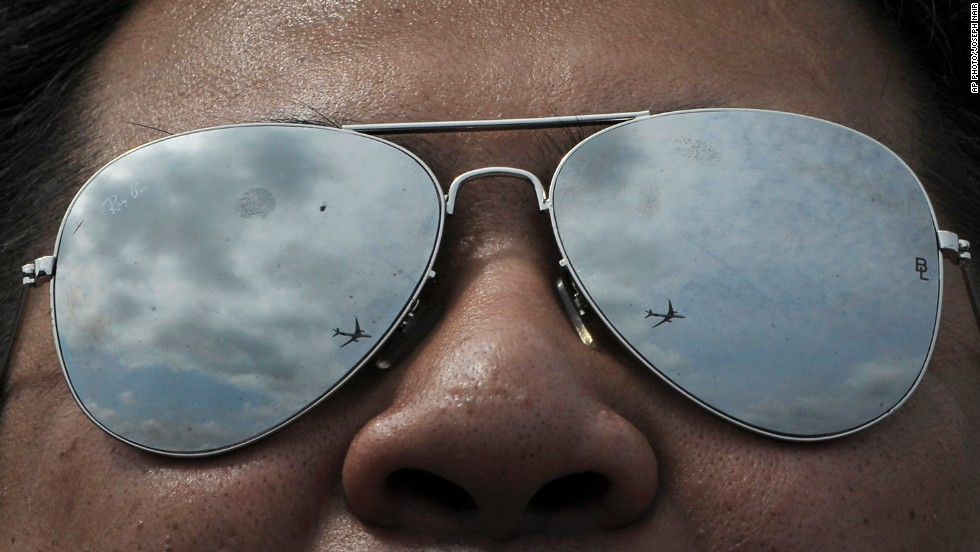 A visitor watches an aerial display at the Singapore Airshow on Feb. 12, 2014.