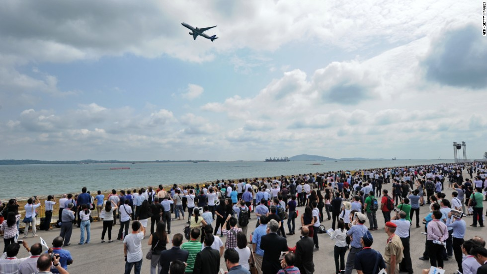 The crowd watches the A380 plow through the sky.