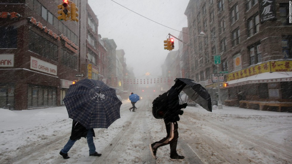 People walk through snow February 13 in the Chinatown neighborhood of New York City.