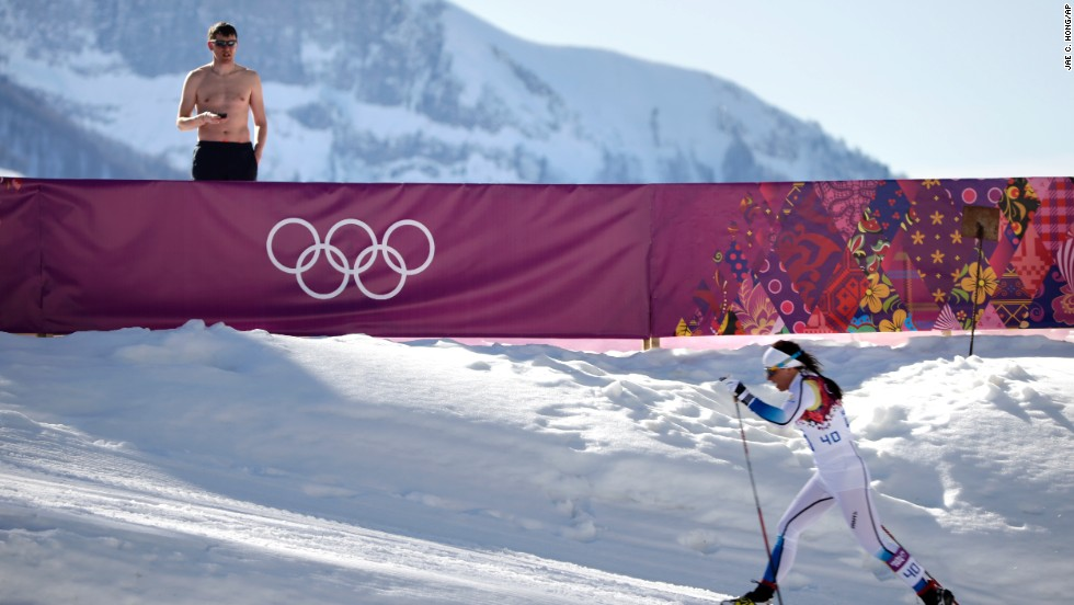 A shirtless spectator watches Swedish cross-country skier Charlotte Kalla compete during the women's 10-kilometer classic on February 13.