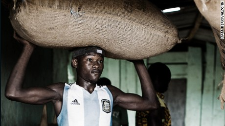 Worker on an Ivorian cocoa farm carries a sack of cocoa beans on his head