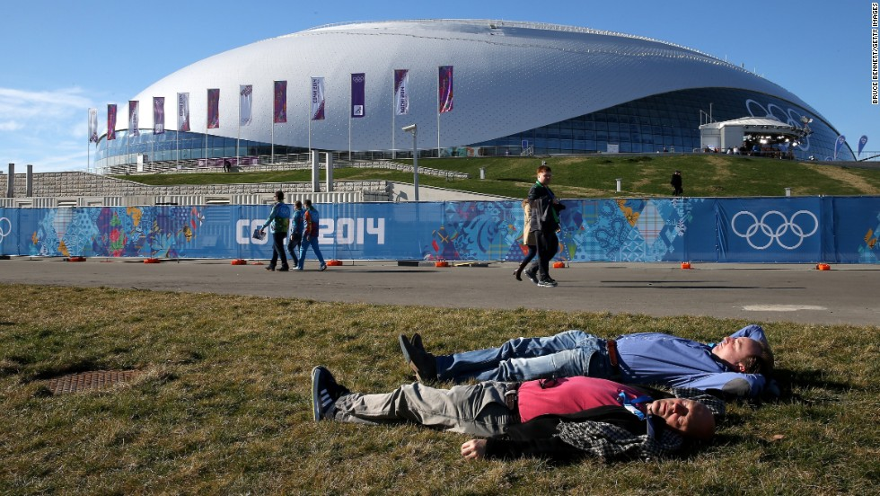 People lie on the grass outside of the Bolshoy Ice Dome in Sochi on Thursday, February 13.
