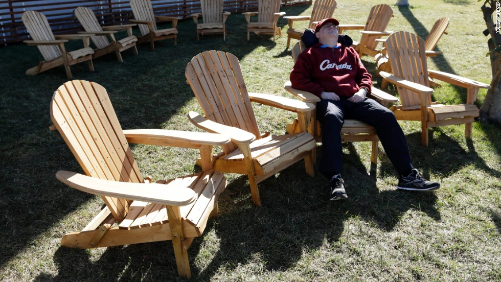 A spectator takes a break in the sun outside the Canada House in the Olympic Park on February 13.