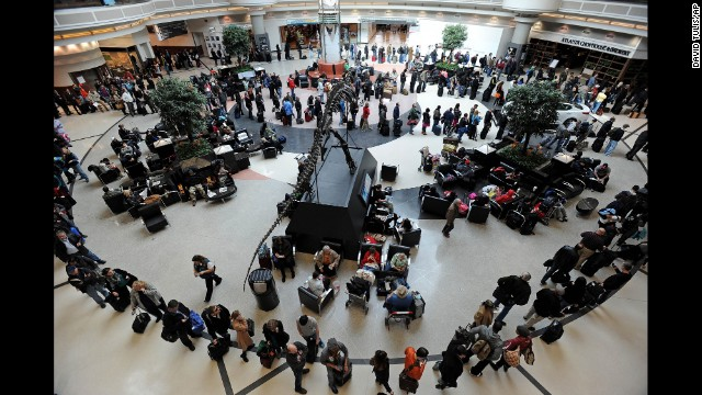 A long line of travelers winds around the atrium of Hartsfield-Jackson International Airport in Altanta on Thursday, February 13, as people attempt to catch flights previously canceled due to the massive winter storm.