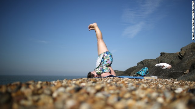 "A woman practices yoga on a British beach. Suzanne Steinbaum says ""living from the heart"" includes reducing stress."