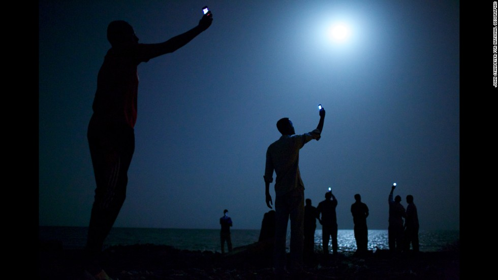 <strong>World Press Photo of the Year 2013: </strong>African migrants on the shore of Djibouti raise their phones in an attempt to capture an inexpensive signal from neighboring Somalia, a tenuous link to relatives abroad. Djibouti is a common stop-off point for migrants on their way from such countries as Somalia, Ethiopia and Eritrea, seeking a better life in Europe and the Middle East. The following are a selection of the other World Press Photo winners.
