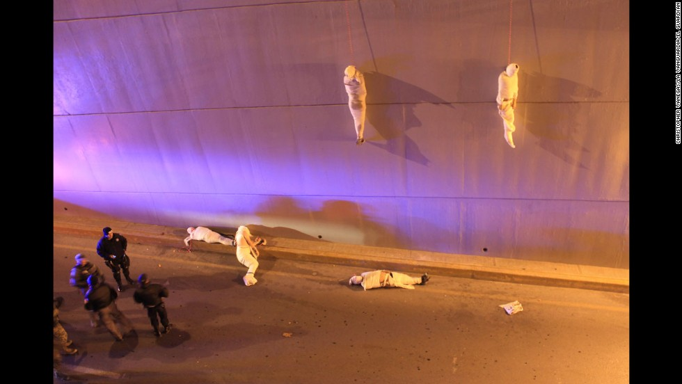 <strong>3rd Prize Contemporary Issues Single: </strong>Police arrive at a crime scene where two organized crime victims hang from a bridge in Saltillo, Mexico; another three are on the ground.