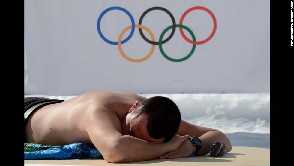 An Olympic volunteer sunbathes before a cross-country skiing event Friday, February 14.