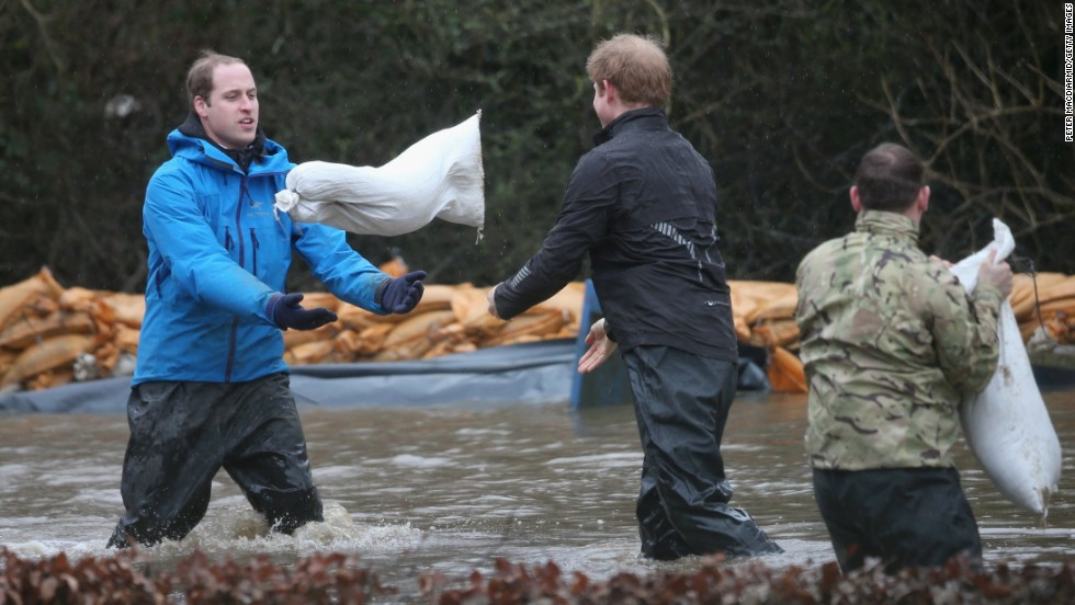 The princes toss sandbags to each other as they help with flood defense efforts February 14.