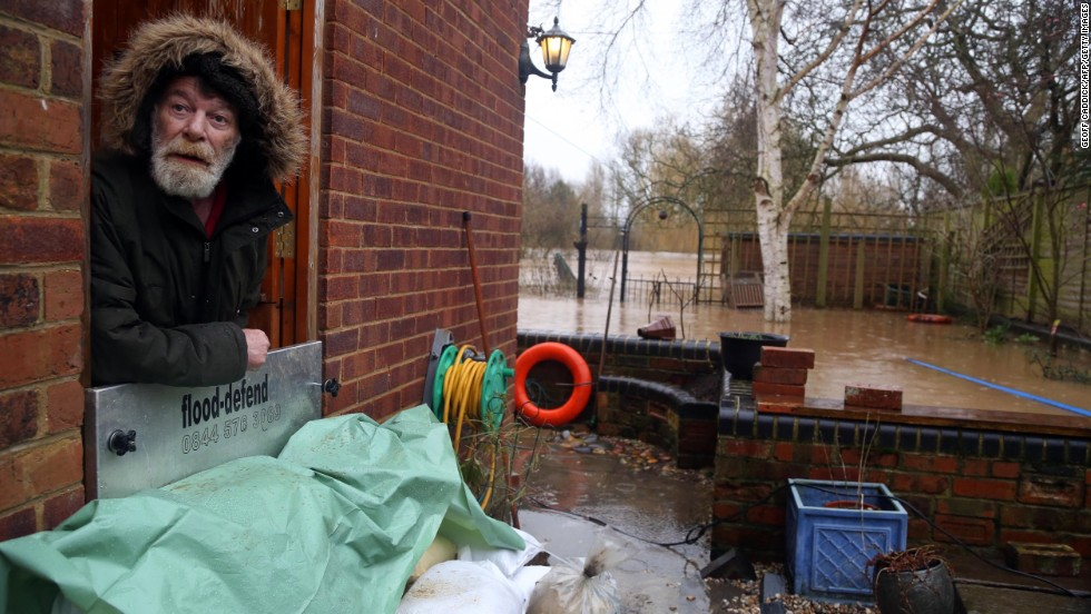 Richard Perry looks out the back door of his house in Gloucester, England, as the River Severn rises to record heights.
