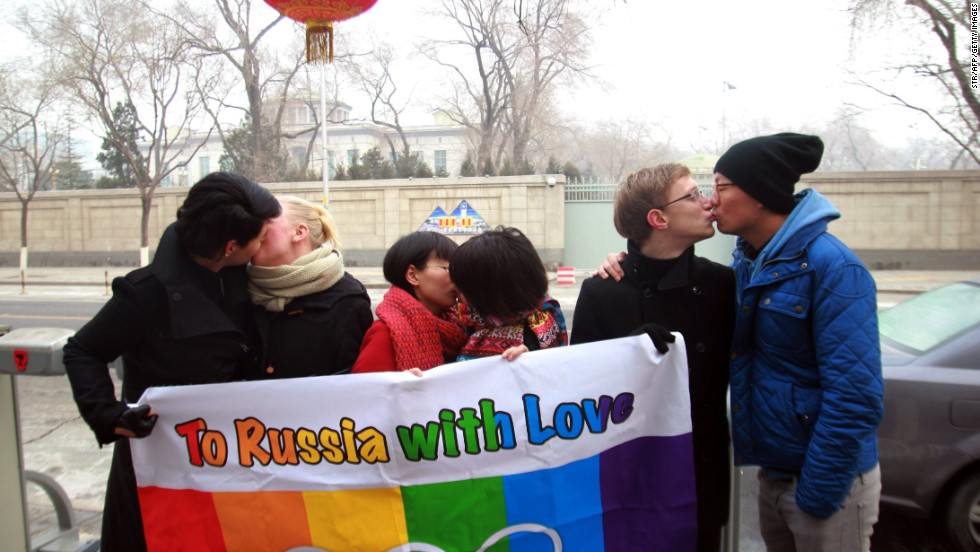 "It wasn't just Winter Olympians celebrating Valentine's Day. Here a group of gay and lesbian activists hold a banner of the rainbow flag, the Olympic rings and the words ""To Russia with love"" as they stage a Valentine's Day kissing protest in Beijing."