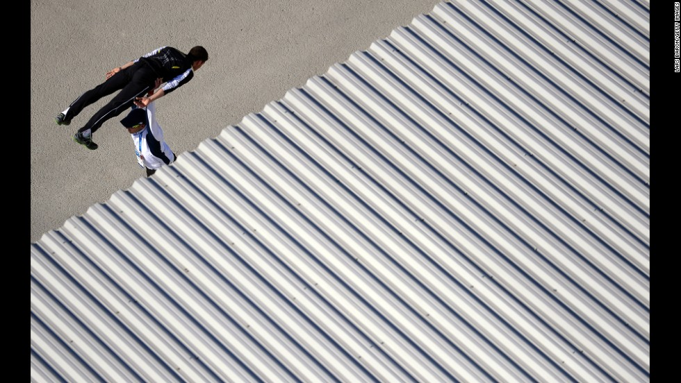 A ski jumper warms up with his coach prior to training on February 15.