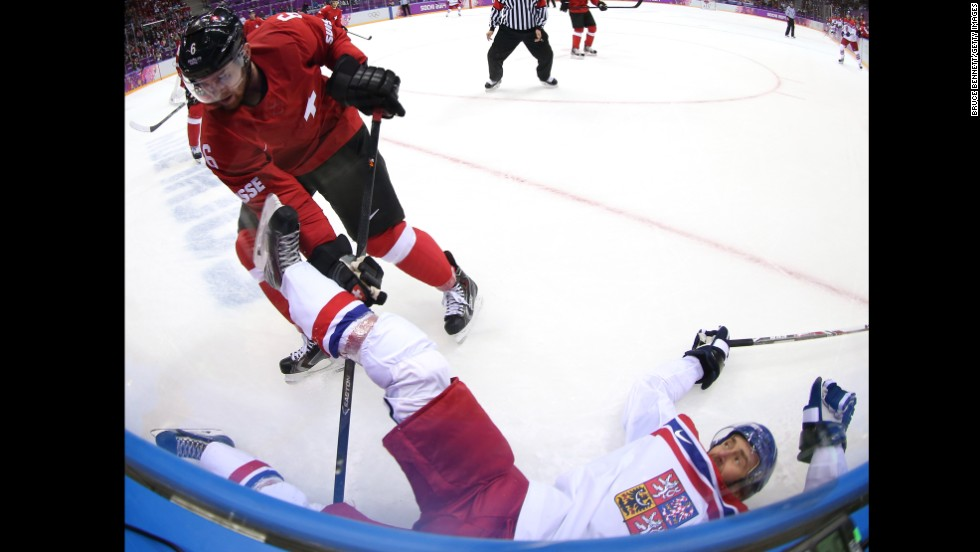 Petr Nedved of the Czech Republic falls to the ice after being checked by Switzerland's Yannick Weber during the men's hockey game on February 15.