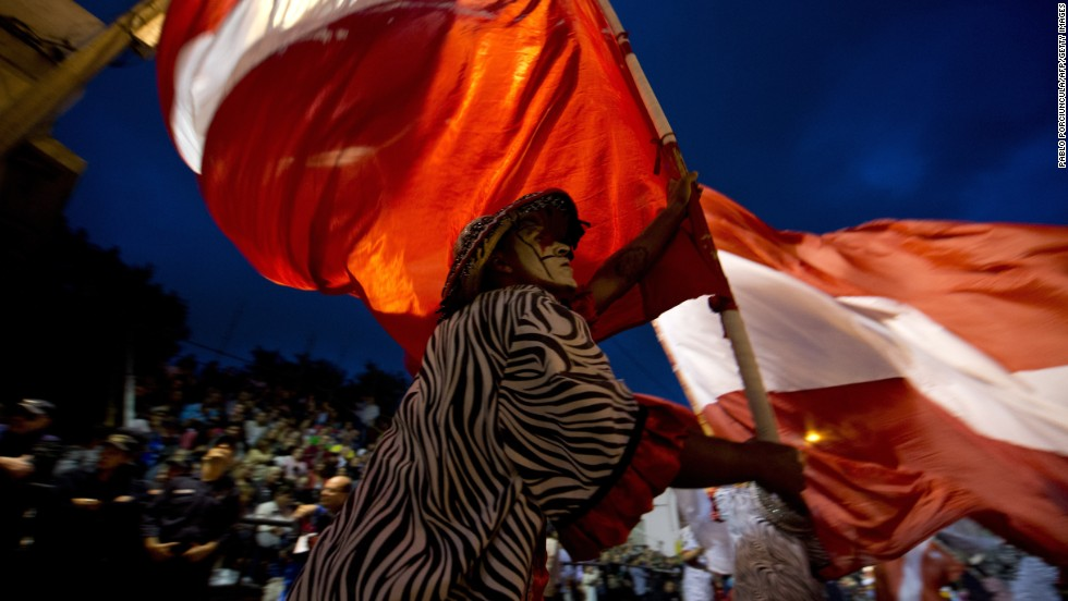 A reveler carrying a giant flag performs in Montevideo on February 14.