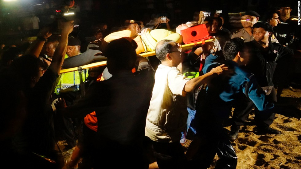 """Volunteers carry a rescued diver Monday. The area in which the women were diving is a noted beauty spot, """"but it's also very dangerous,"""" said Bali Governor I Made Mangku Pastika, citing """"unpredictable natural aspects."""""""
