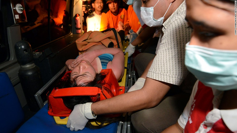 One of the Japanese divers is carried onto an ambulance.