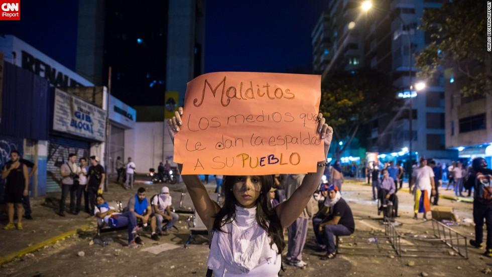 Una joven levantando un cartel frente a los efectivos de la Policía Nacional Bolivariana en la Av. Luis Roche de Altamira