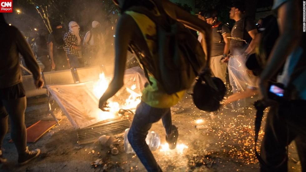 Manifestantes apagan el fuego que otros manifestantes iniciaron en la Av. Luis Roche.