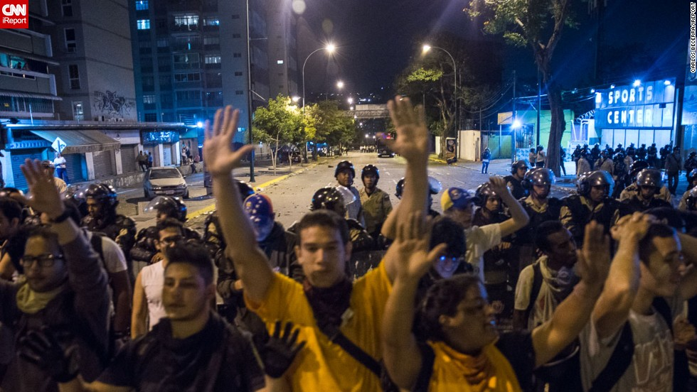 Las manos alzadas de los manifestantes pidiendo que cesen las manifestaciones violentas.