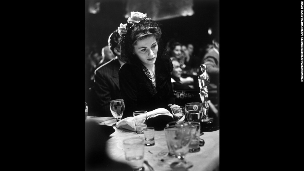"""Joan Fontaine looks at the best actress Oscar she won for her role in the film """"Suspicion."""""""