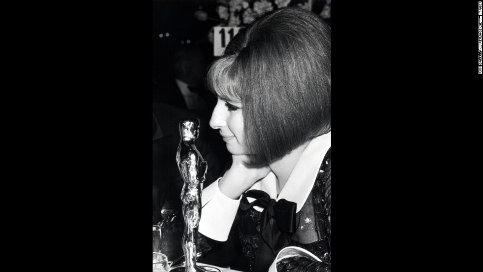 "Barbra Streisand gazes at the best actress statuette she won for ""Funny Girl."" There was a tie for the award in 1969, with the other winner being Katharine Hepburn."