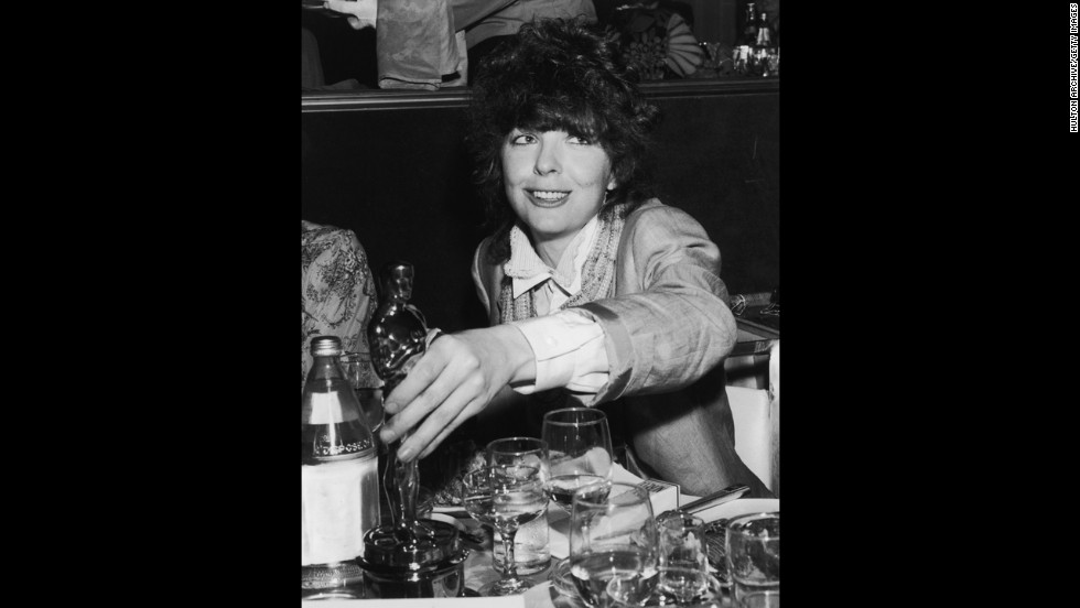 """Diane Keaton places her Oscar on a restaurant table after the Academy Awards ceremony in 1978. She received the award for her role in """"Annie Hall."""""""