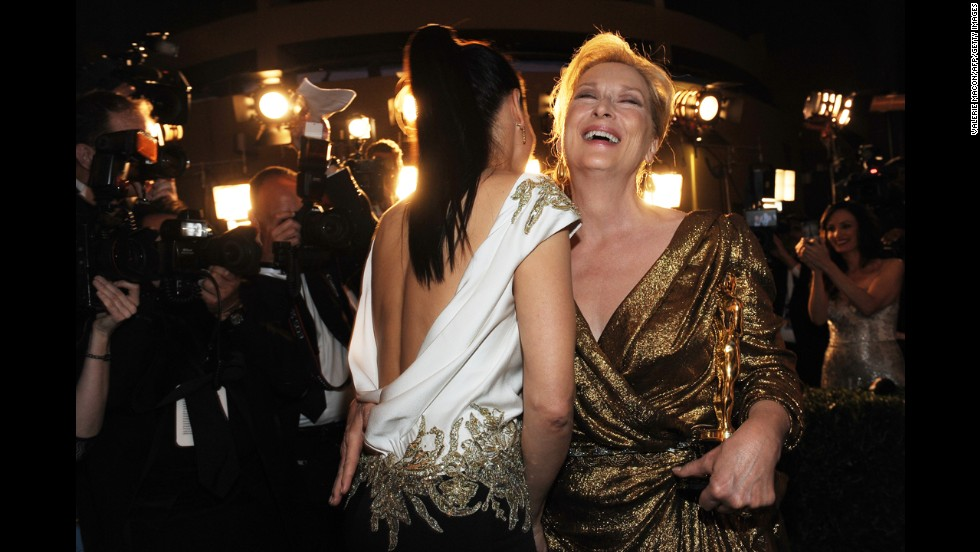 "Meryl Streep, right, laughs with Sandra Bullock after Streep's win for her role in ""The Iron Lady."""
