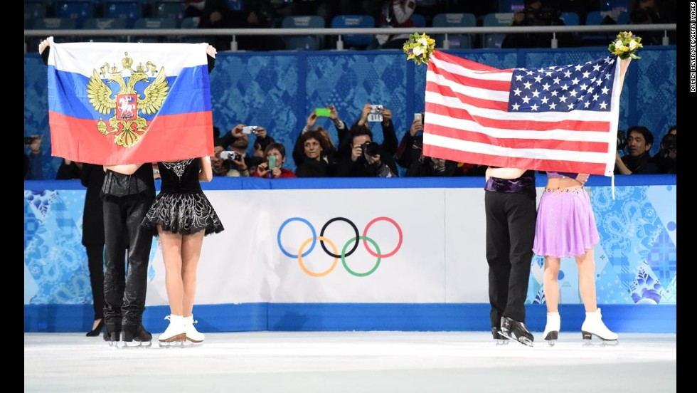 Russians Nikita Katsalapov and Elena Ilinykh, left, and Americans Meryl Davis and Charlie White celebrate during the flower ceremony for the Olympic ice dancing competition Monday, February 17. The Americans won gold and the Russians won bronze.